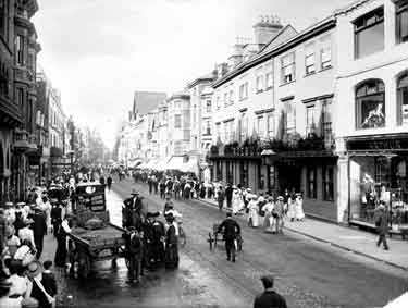 Cornmarket Street, Oxford, Oxfordshire. Looking north along the street showing crowds of people walking past the Victorian shops on either side of the road. A horse drawn delivery dray has parked behing a motorised vehicle at the edge of the road foregrou