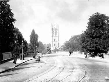 Magdalen College, Oxford, Oxfordshire. The familiar late 15th century college tower from the bridge, with a tram making its way into town and people cycling and walking.