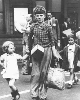 Evacuees, a young boy with a small girl, carrying carriers bags and a gas mask box about his neck, arriving at the Oxford railway station, 9.1939